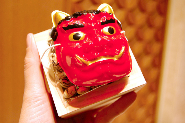 Mini oni demon mask with soybeans in wooden sake masu box at Mitsukoshi in Tokyo, Japan on Setsubun (WBEZ/Louisa Chu)