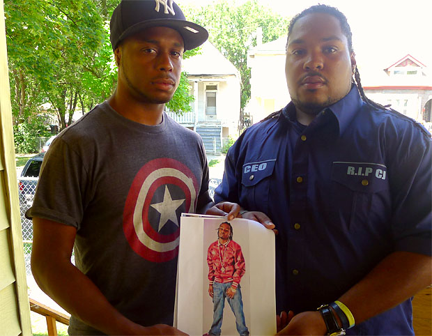 Toussaint Reed and Malcolm Rashad hold a picture of their slain friend Cornelius Jordan. They say the West Englewood native was mislabeled as a gang member at the time of his shooting death. (WBEZ/Natalie Moore)