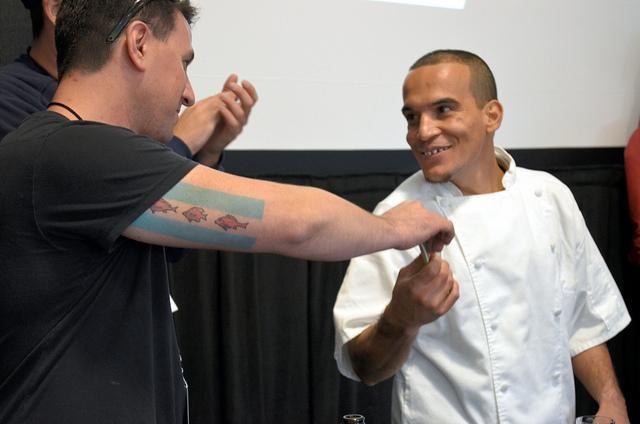 Supreme Lobster fishmonger Carl Galvan awards winner Luis Pedroza of Benny's Chop House $2,000 cash prize at Supreme Shucker 2012 (WBEZ/Louisa Chu)
