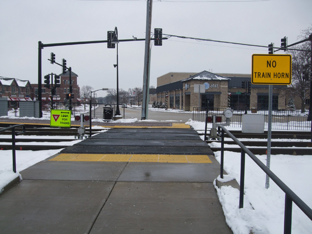 Signage at Metra's Bartlett station on the Milwaukee District/West Line route indicates safety precautions for pedestrians crossing the tracks. (Flickr/Steven Vance)