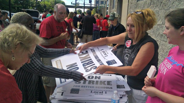 Teachers pick up 'on strike' signs Saturday at a 'strike headquarters' the Chicago Teachers Union has set up. (AP)