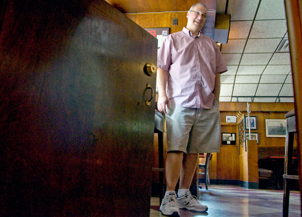 Paul Tuzi, one of the owners of Lincoln Park's Twin Anchors Restaurant & Tavern, shows off a half-size door at the back of the bar, which he says was installed during prohibition to enable quick escapes. (Photo by Chris Bentley)