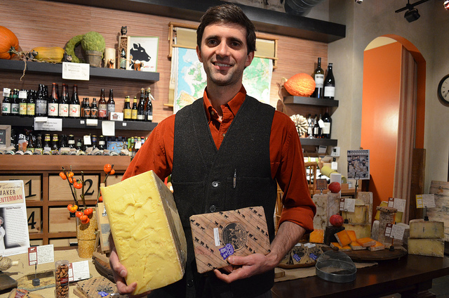 Cheesemaker Andy Hatch with Pleasant Ridge Reserve 80 pound quarter wheel and slice at Fromagination in Madison, Wisconsin (WBEZ/Louisa Chu)