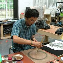 Image 1 - Artist Masashi demonstrating Japanese painting techniques during our open studio exhibition for the Artists and Makers Festival
