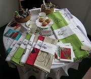Display of work for sale: tea towels, table cloths, and cards
