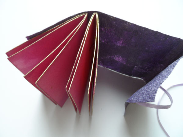Handmade paper cloth cover, pamphlet stitch binding, hand coloured pages, ribbon close