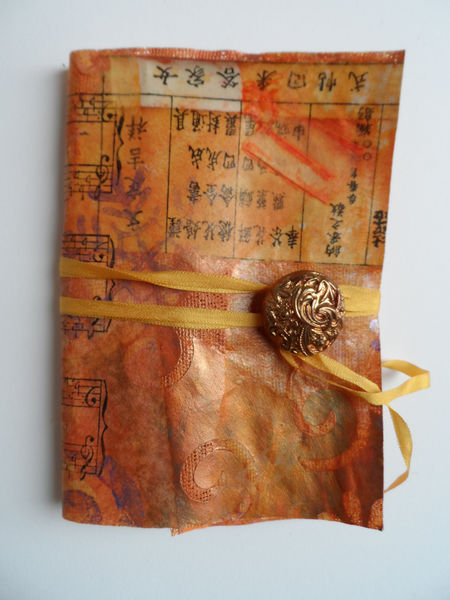 Handmade paper cloth cover, pamphlet stitch binding, ribbon and button close