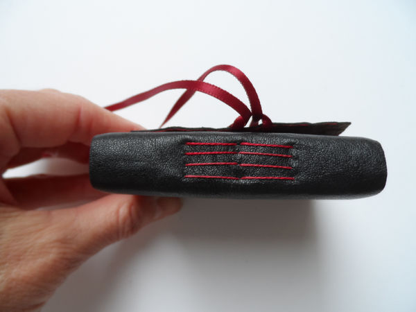 Leather cover with exposed pamphlet stitch and ribbon close