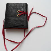 Leather cover lined with red andd gold coloured paper, ribbon close