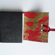 Leather cover lined with red and gold paper, ribbon closure