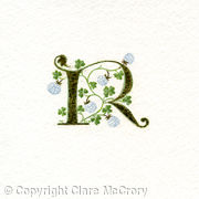 Gold leaf manuscript letter R with white clover on watercolour paper