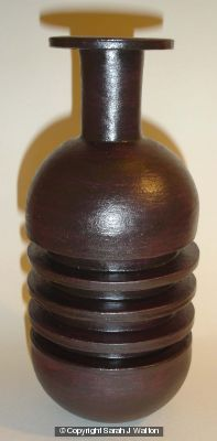 Black stoneware bottle with three ribs