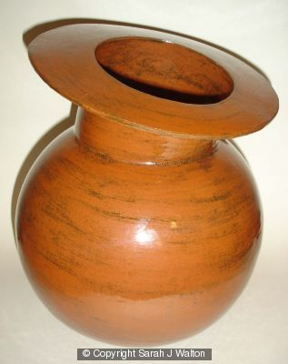 Stoneware pot with spherical body and tilted rim.