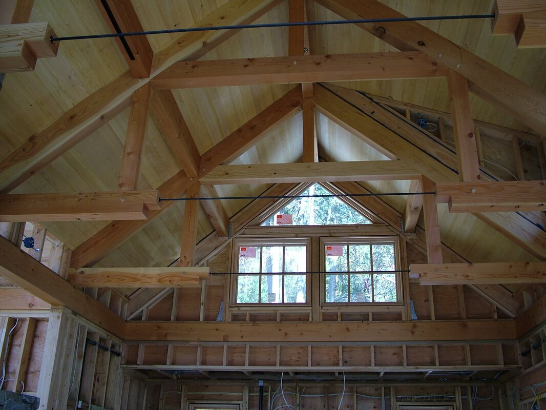 Timber framed trusses under construction.