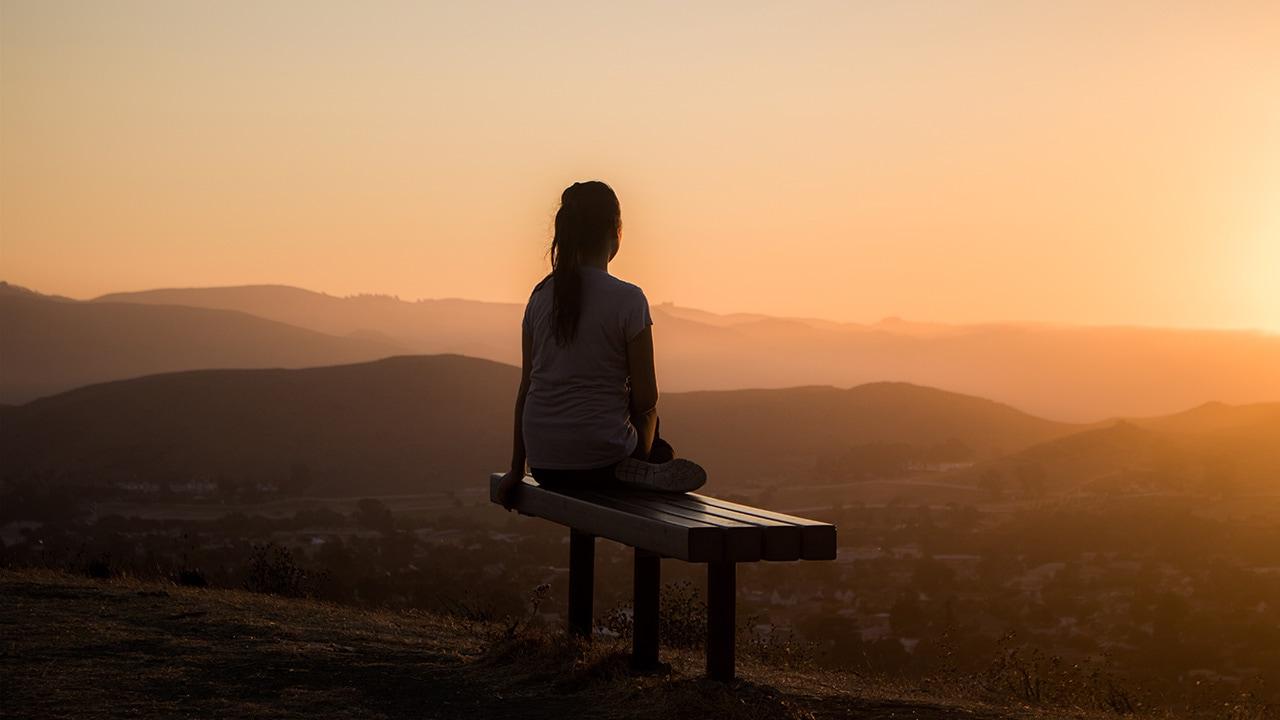 Une femme assise sur un banc en train de regarder le coucher du soleil