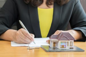 Businesswoman signing a contract for real estate investing