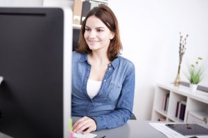 Businesswoman smiling as she works at her desktop while sitting at her desk, view past the edge of the monitor