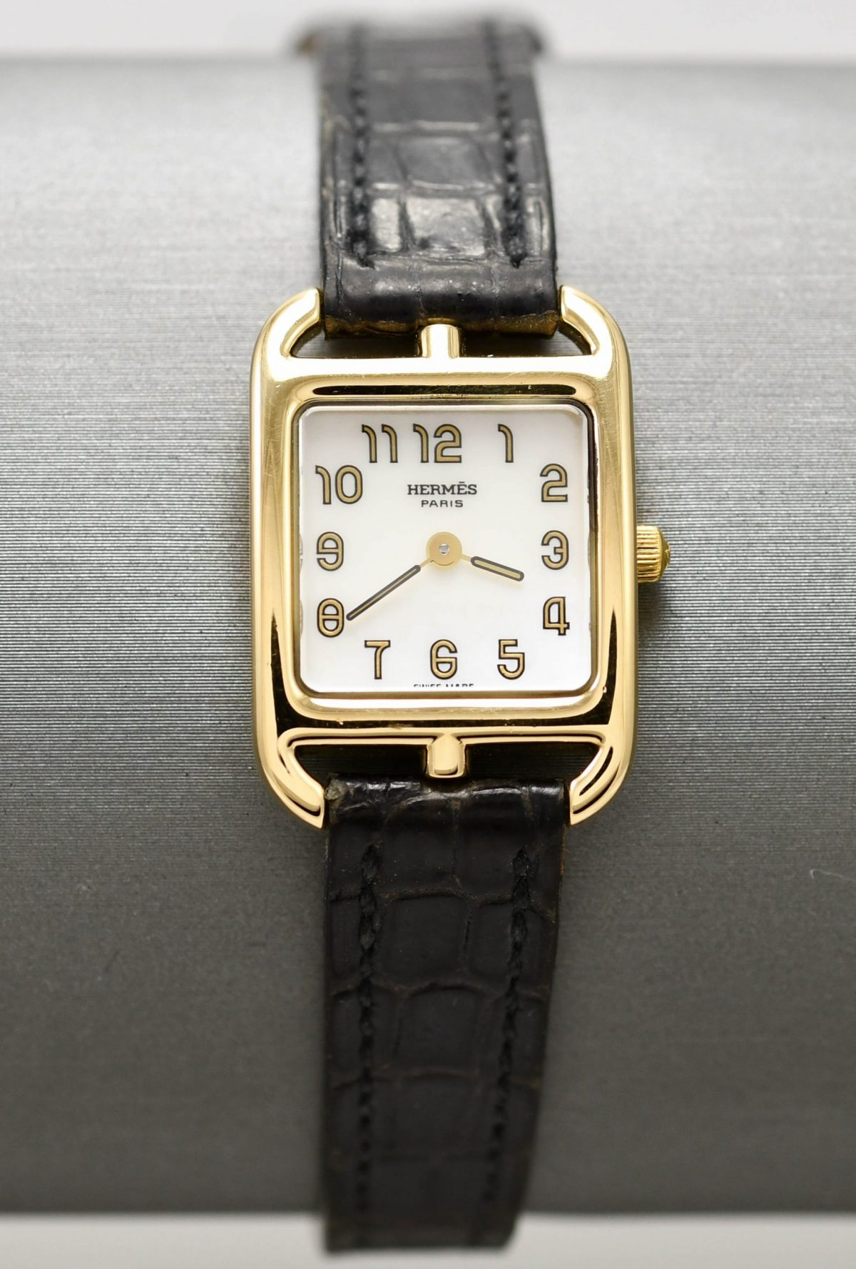 Ladies designer wristwatch by Hermes with 18k yellow gold case and mother of pearl dial.