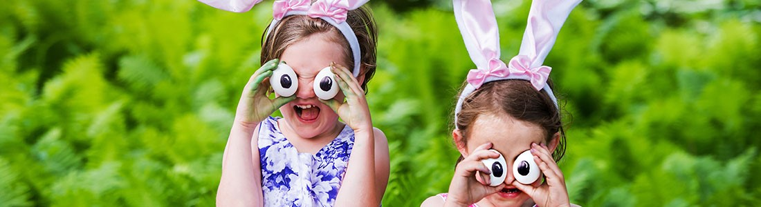 Two little girls holding fake cartoon eyes and smiling