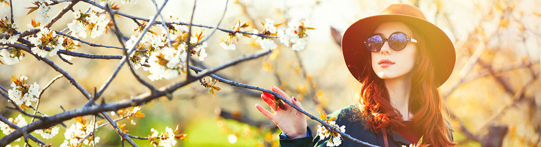 A girl with a hat and sunglasses looking at flowers - Healthy Vision Month