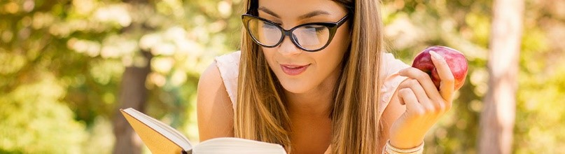 A girl wearing sunglasses eating an apple and reading a book