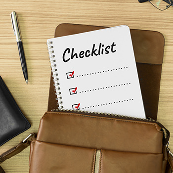 A Checklist in a purse, around it a wallet, pencil, glasses and a phone