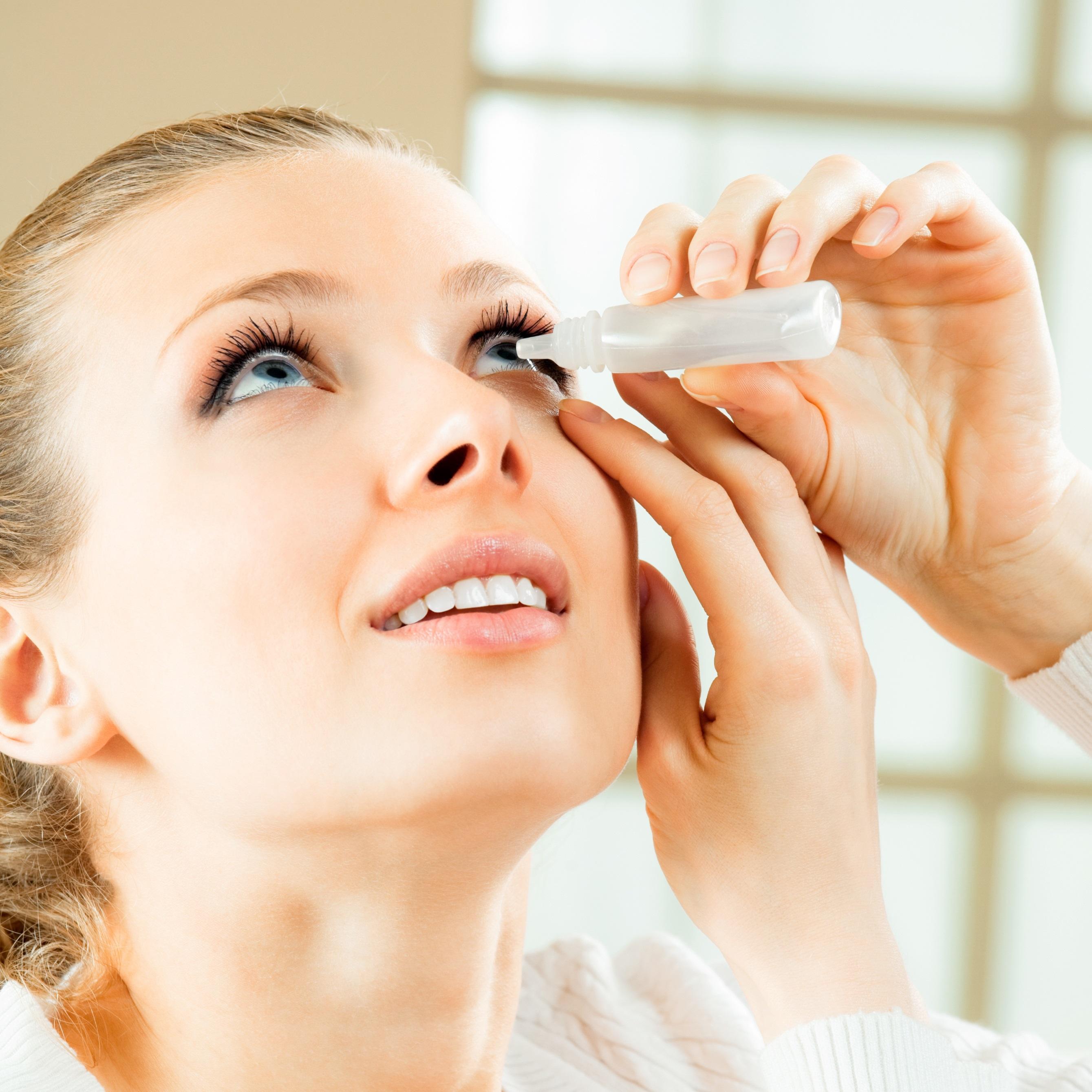 Woman putting in eye drops