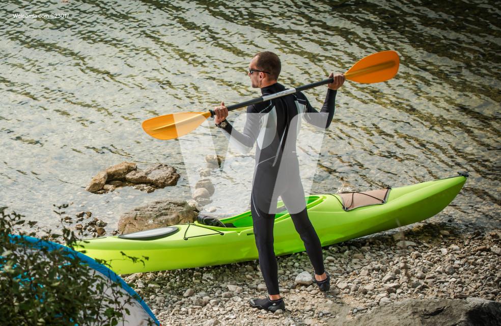 Man By Lake Preparing For Kayaking.