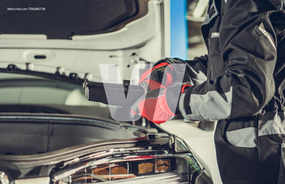 Car Mechanic Looking For Burned Fuse Under Vehicle Hood