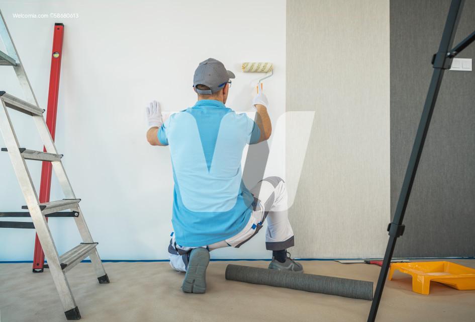 Caucasian Men Installing Vinyl Wallpaper