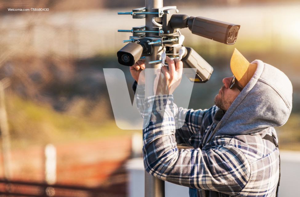 CCTV Technician Installing IP Cameras on a Pole