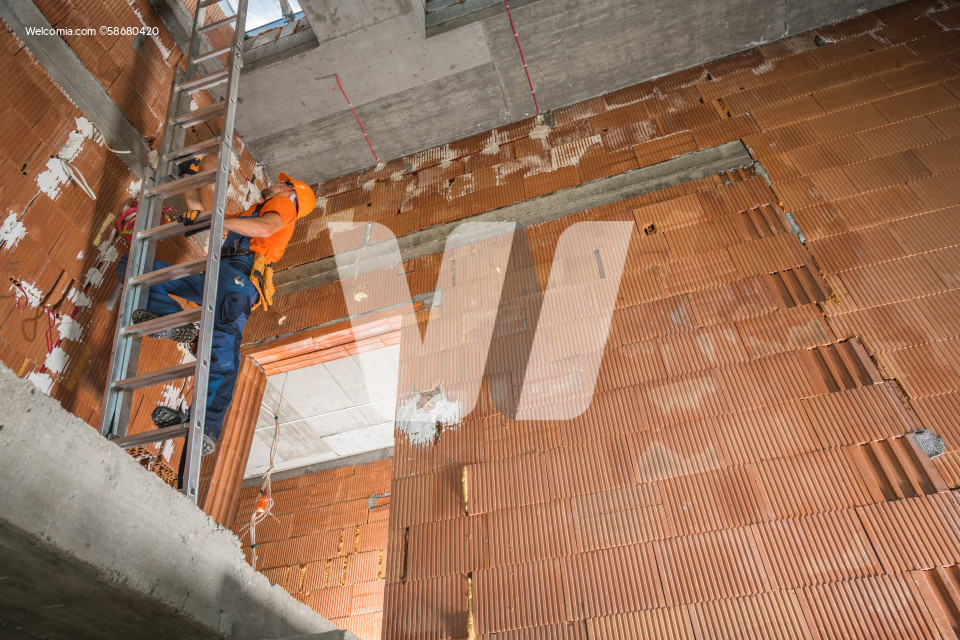 Construction Worker on a Ladder Inside Commercial Building