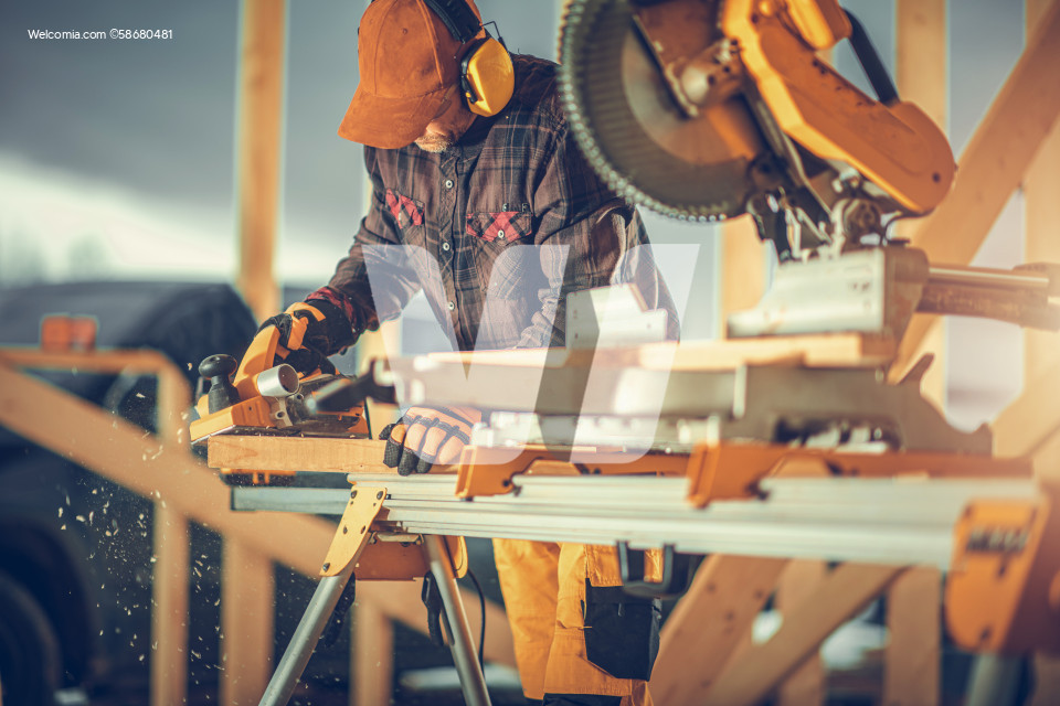 Construction Worker Planing Wood with Electric Planer