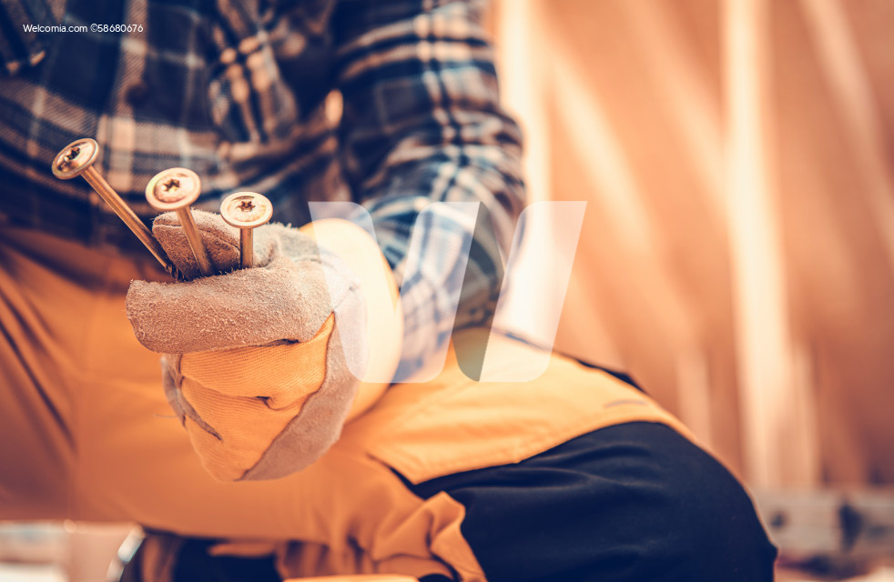 Construction Worker with Heavy Duty Wood Screw in His Hands