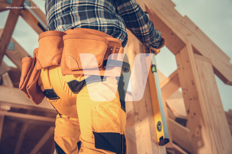 Contractor Using Spirit Level While Building Wooden House Frame