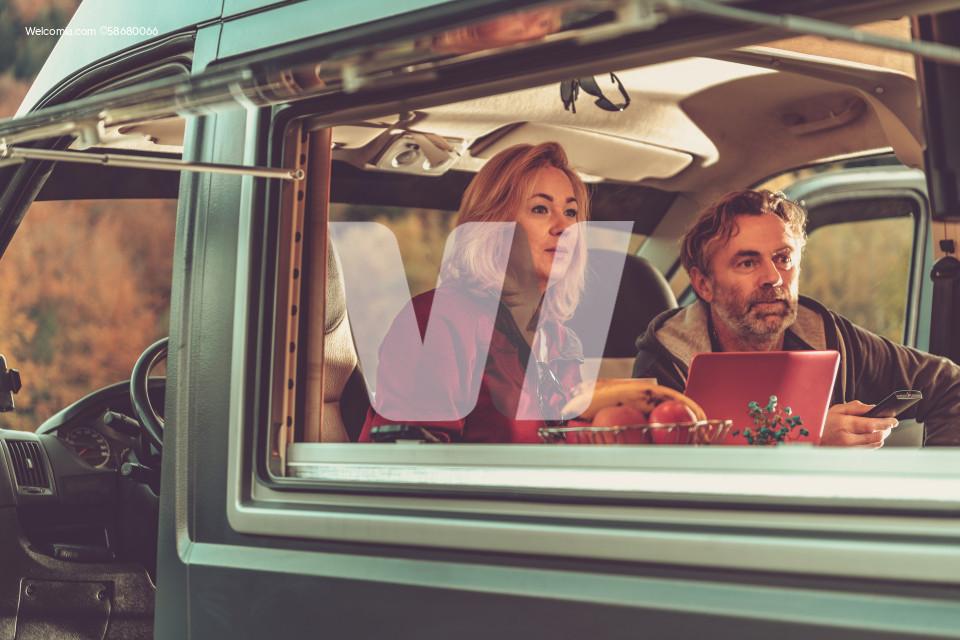 Couple Watching Exciting TV Game Inside Camper Van RV
