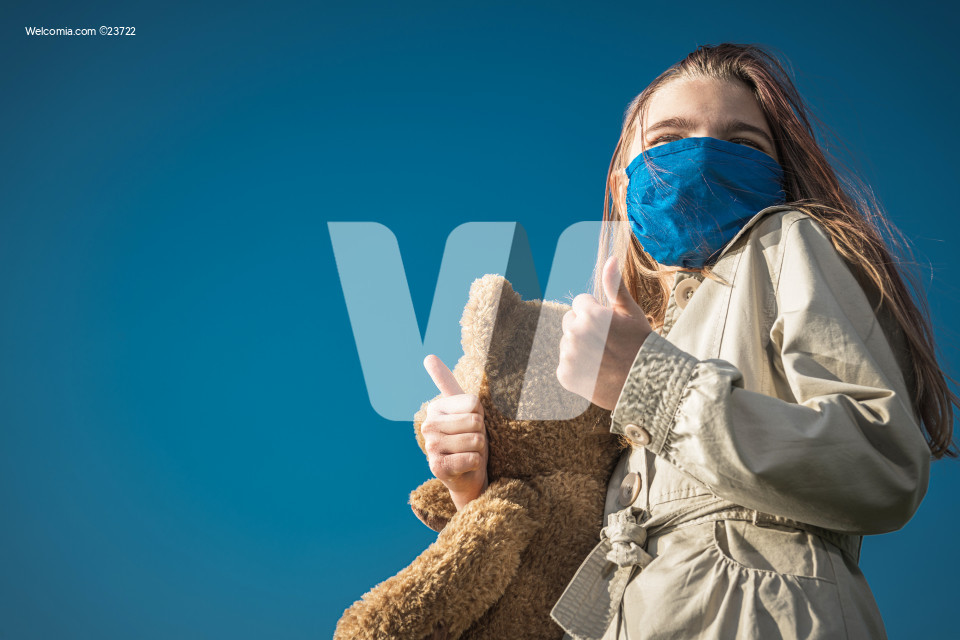 Girl in Face Mask Holding Large Teddy Bear