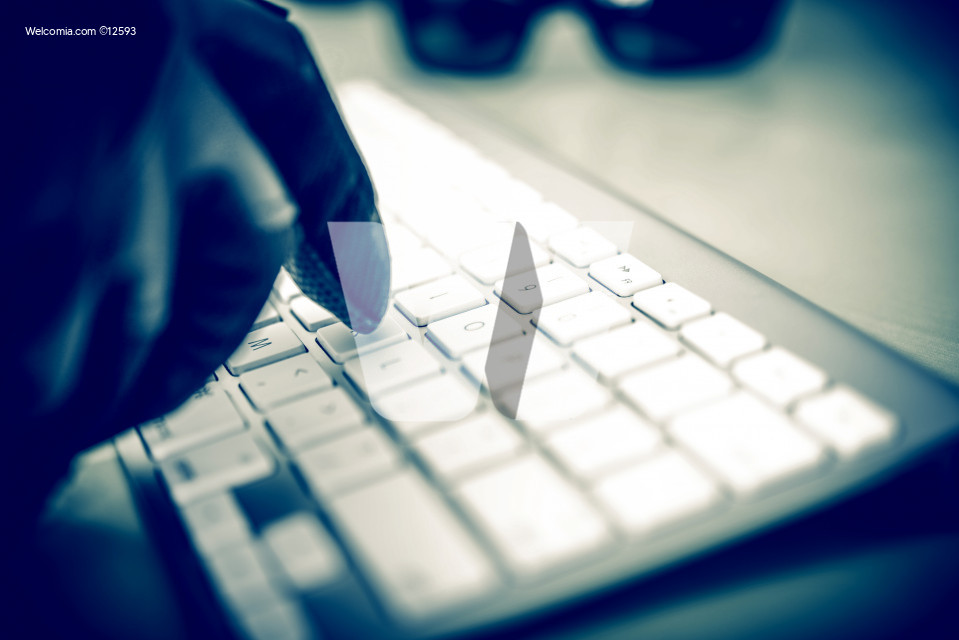 Hacker in Work. Hacker Hand in Black Glove Typing on the Keyboard. Closeup Photo Concept.