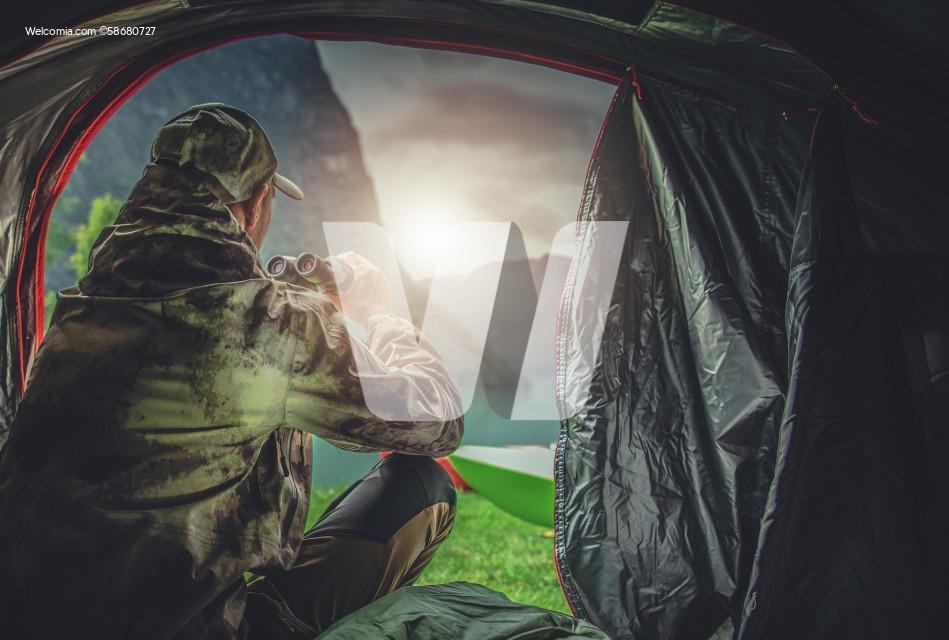 Hunter in His 40s Spotting Wildlife Using Binoculars