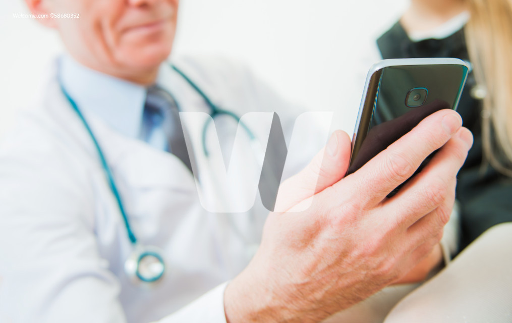 Medical Doctor Looking at His Smartphone Device