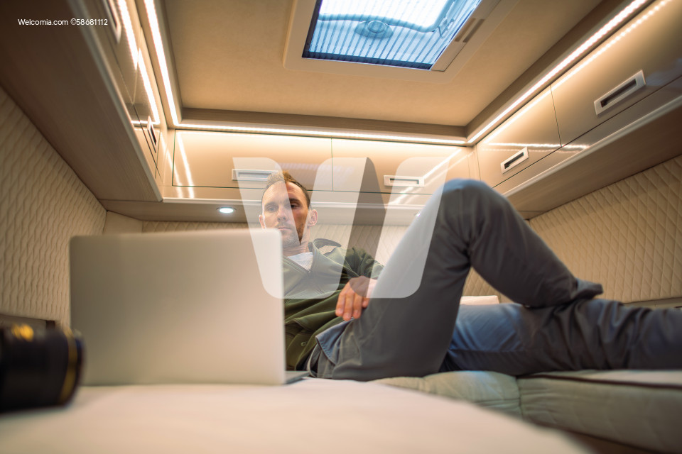 Men Laying in His RV Camper Van Bed and Watching Movies