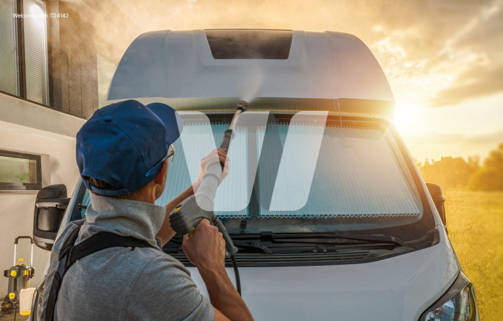 Men Pressure Washing His Camper Van RV During Scenic Sunset
