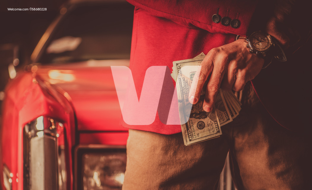 Men with Pile of Cash Money in Front of His Classic Car
