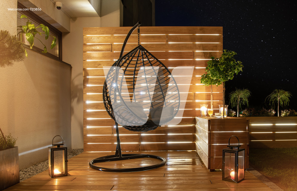 Night Time in Stylish Garden with Wooden Porch and Planters Illuminated by LED Lights.