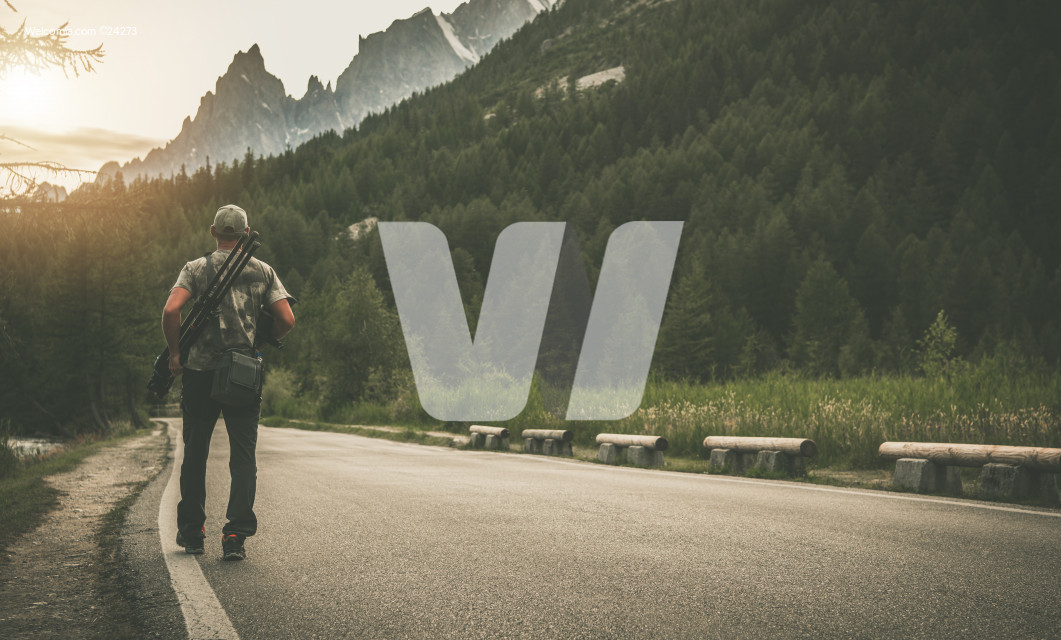 Photographer with Camera and Tripod Walking Along Mountain Road