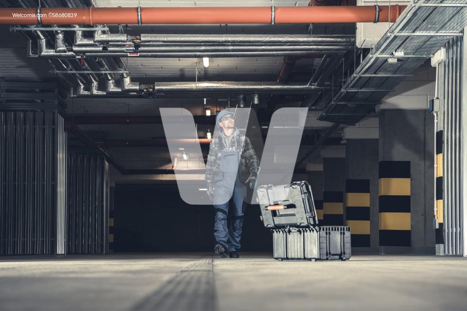 Plumbing Technician Walking Along Underground Parking
