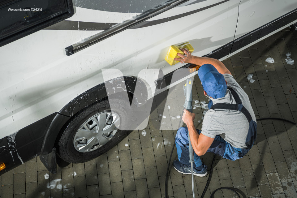RV Camper Owner Washing Vehicle.