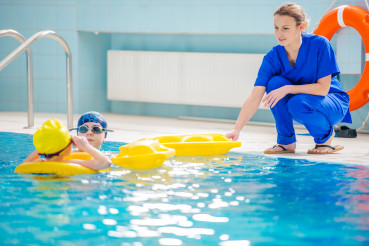 Aquatic Rehabilitation With Therapist And Two Patients.