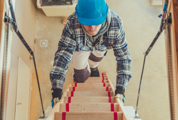 Worker Climbing on Attic Stairs