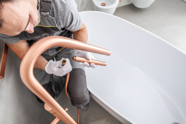 Handyman Attaches Faucet Kit To Complete Tub Installation.